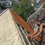 Aanbrengen van nieuwe dakpannen.